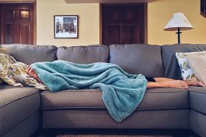 Pessoa passando mal e deitada no sofá.