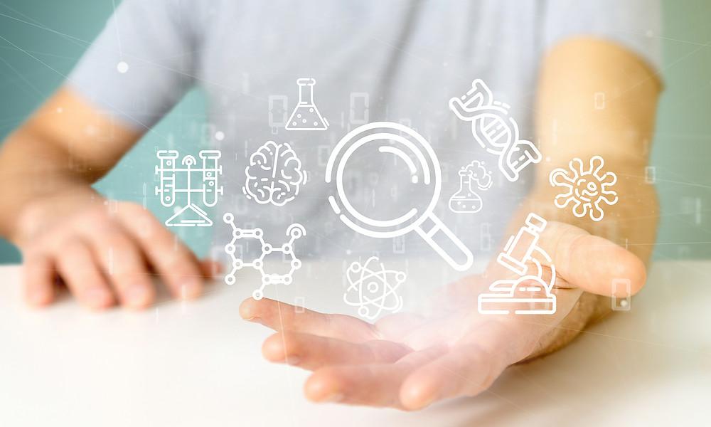 homem com a mão sobre uma mesa, com a palma da mão voltada para cima, com ícones como lupa, microscópio, DNA e cérebro, pairando sobre sua mão