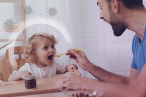um pai alimentando uma criança pra melhor o sistema imunologicos