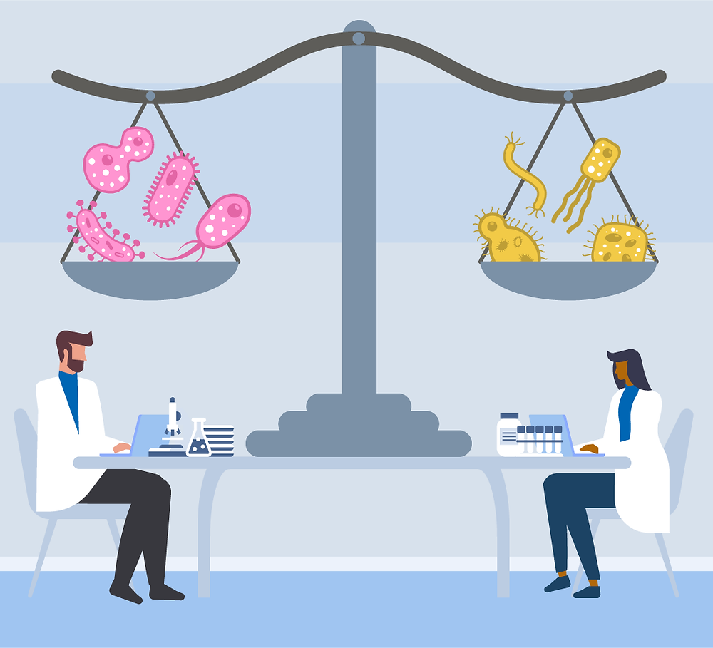 uma balança gigante, com bactérias em equilíbio, sobre uma mesa. Dois cientistas sentados a mesa trabalhando