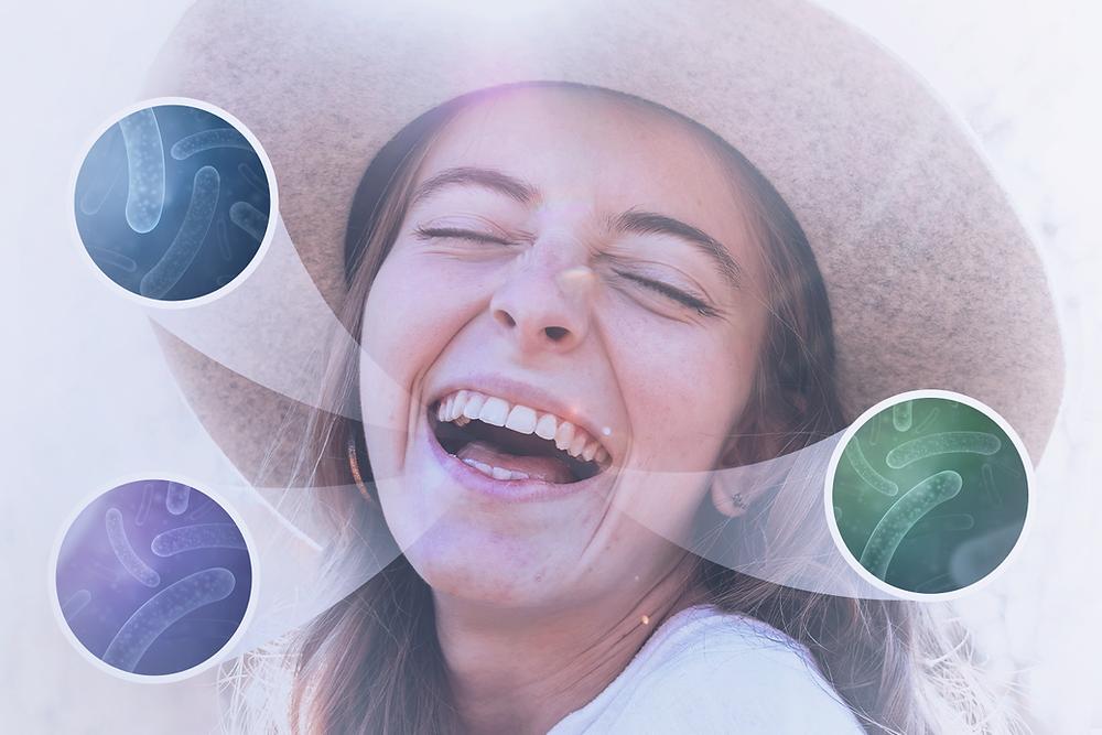 menina sorrindo com destaque nos microrganismos presentes na boca