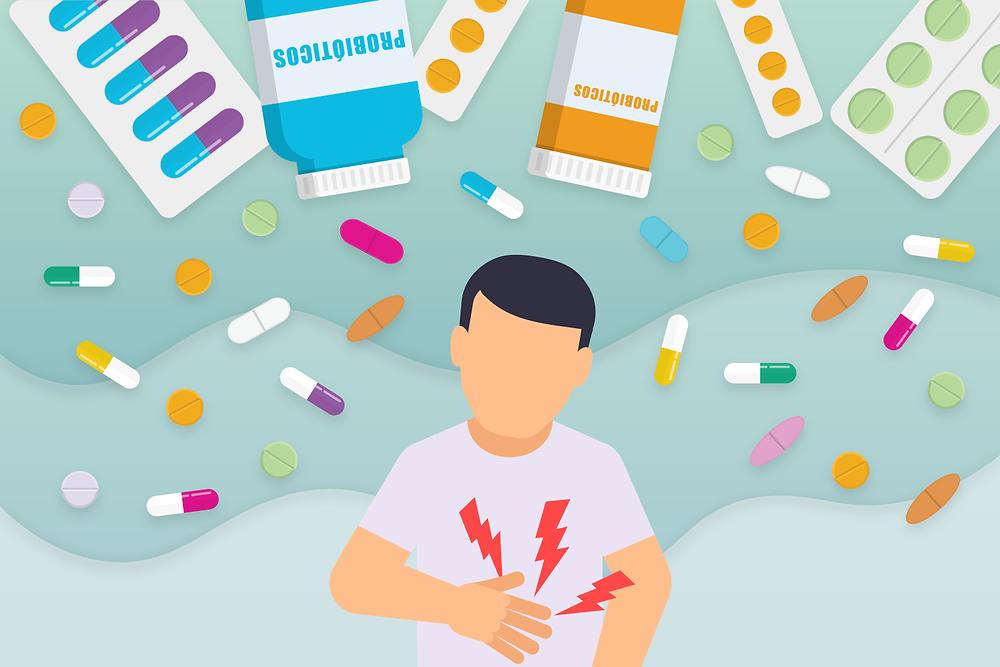 Homem com dor estomacal. Comprimidos e capsulas de remédio e probiótico circulando o homems