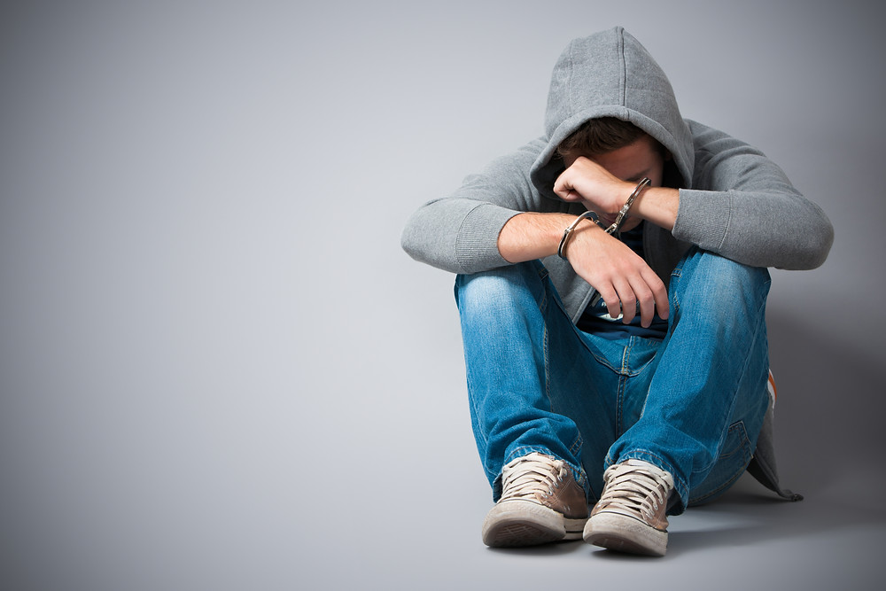 teenager in grey hoodie, blue jeans and white trainers huddled on floor with head down with hands in handcuffs