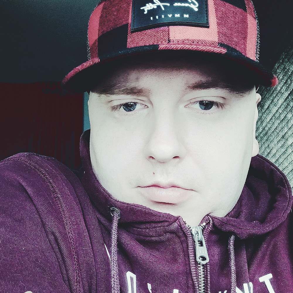 Ben Landy News Reporter for the News Team at the OULS. Ben is wearing a baseball cap which is red and pink checked. He is also wearing a zip up hoodie in burgundy red and is taking a selfie.