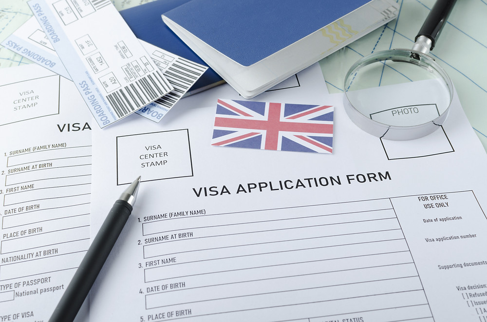 Visa application form, passports, tickets,English flag, magnifying glass on the world map.Concept of checking documents to get a visa