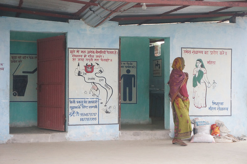 A woman standing outside a sanitation facility in India