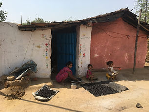 Indian family sitting in front of their home