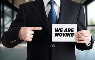 Businessman shows a card with the message we are moving. Business or office relocation con