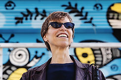 Artist Headshot of Alex Bulmer, a white woman with short light brown hair wearing black cat eye sunglasses and smiling in front of a blue and yellow mural