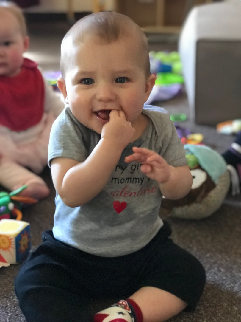 Smiling baby in infant classroom with his fingers in his mouth