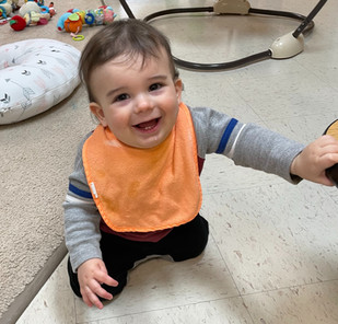 Baby smiling and having fun in the infant program classroom