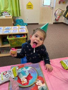 Five year old celebrating her birthday and eating a cupcake in the Pre-K classroom
