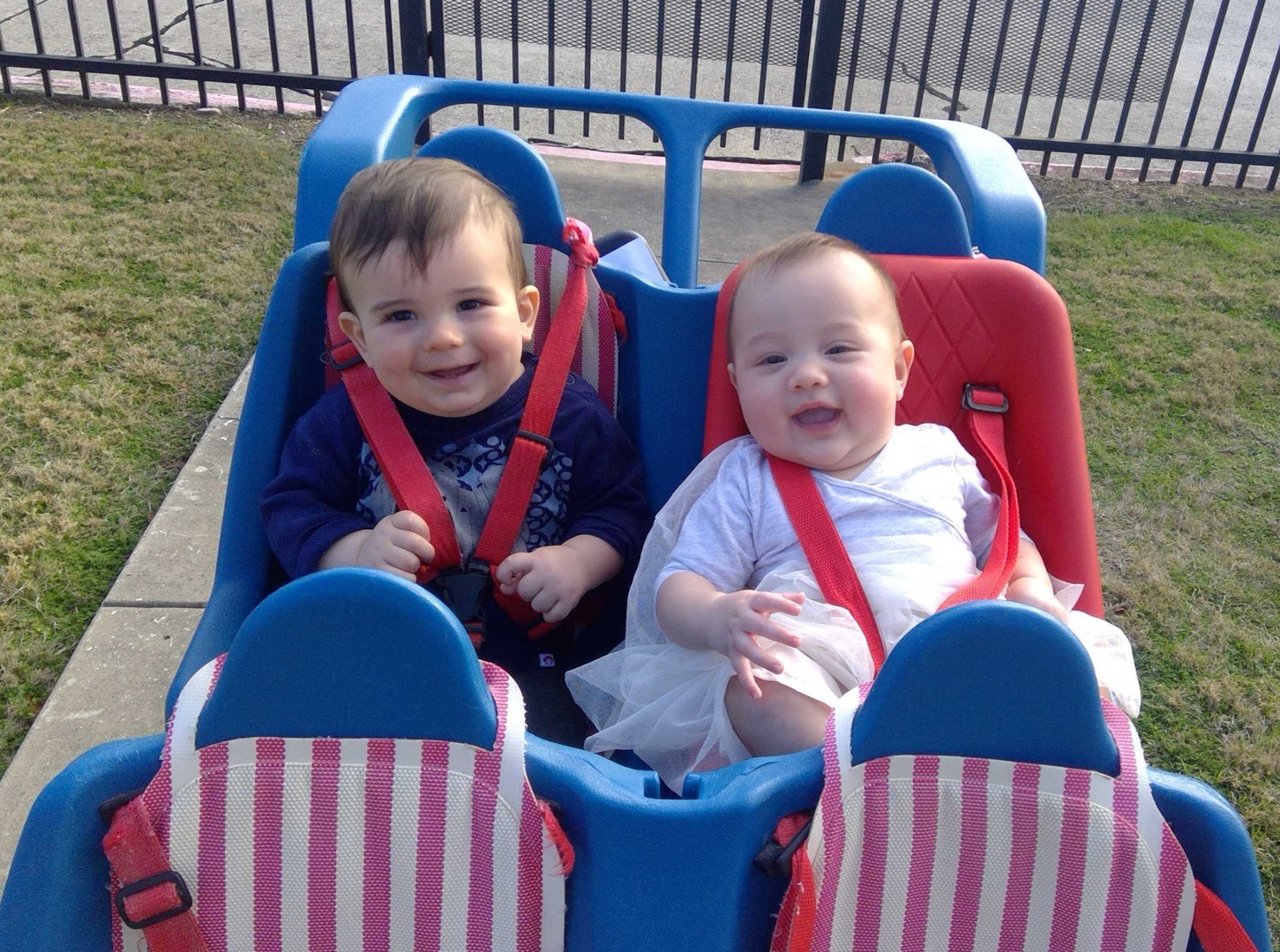 Two smiling infants taking a ride in the buggy at the local daycare