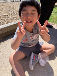 Kid on the playground holding up two peace signs with his hands
