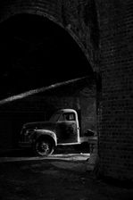 Black and white urban and landscape photography. A dusty, 50s era American Studebaker truck hides in the shadows of a railway bridge near to Stroud, UK