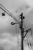 Black and white urban and landscape photography. A pair of trainers hang from telephone and power lines