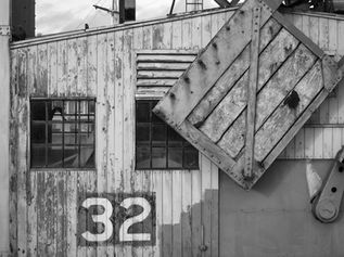 Black and white urban and landscape photography. Detail of lettering and texture on a crane in the harbour in Bristol, UK