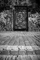 Black and white urban and landscape photography. Graffiti adorns a wooden door set into a stone wall in a cobbled street in Bristol, UK