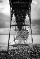 Black and white urban and landscape photography. Intricate iron support structures under the historic pier in Clevedon, UK