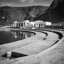 Black and white urban and landscape photography. The curved steps and former changing facilities of an abandoned lido at Tarlair in Scotland stand against a backdrop of dramatic cliffs