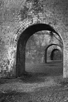 """Black and white urban and landscape photography. Graffiti on a wall in a cascade of arches reads """"Absurd Hero"""""""