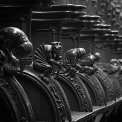 Black and white urban and landscape photography. Ornate carved figures on pews in Seville Cathedral, Spain