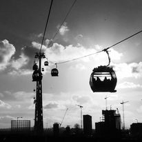 Black and white urban and landscape photography. Cable car gondolas and support tower silhouetted against the setting sun in London Royal Docks, London, UK
