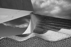 Black and white urban and landscape photography. Ceramic tiles and concrete construction appear as waves at the foot of a communications tower at the Olympic Park, Barcelona