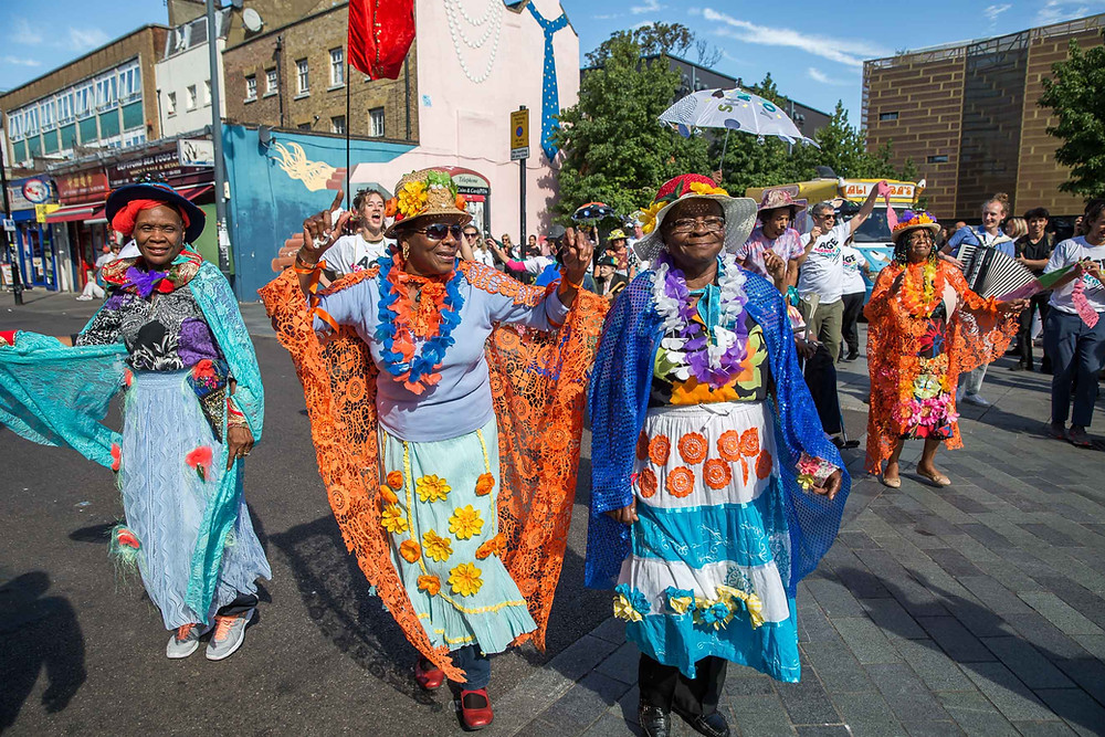 Group of ladies in traditional colourful dresses dancing in the street