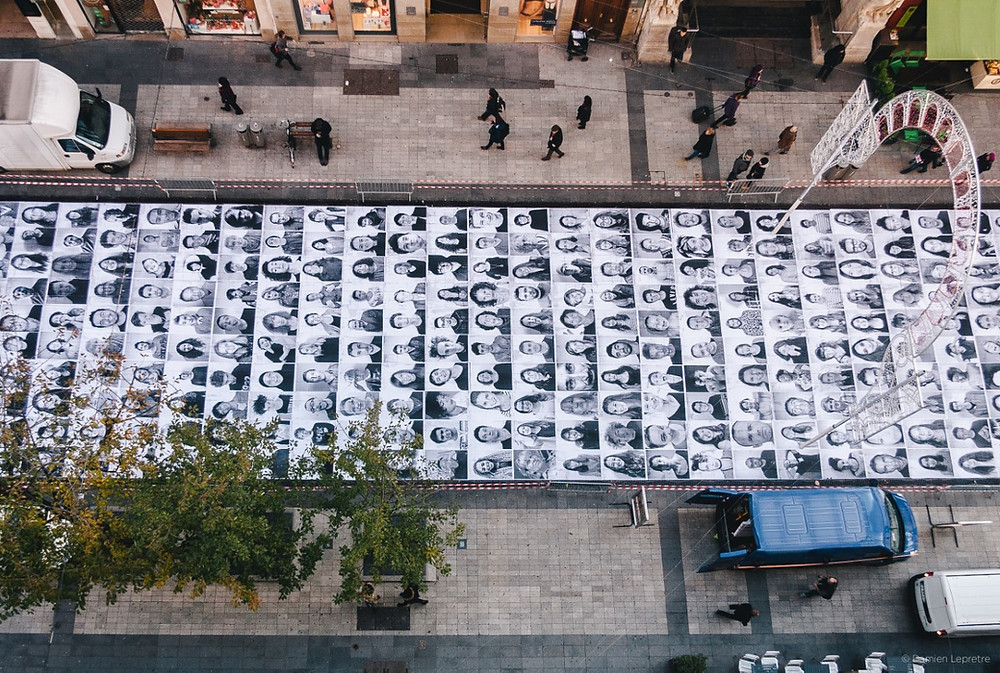 Birds eye view of a street where numerous large black and white portrait photos have been pasted along the road.