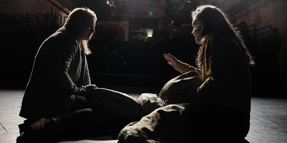 Two women are knelt on a stage, silhouetted against a bright light. They have big bags between them, and one is gesturing to the other.