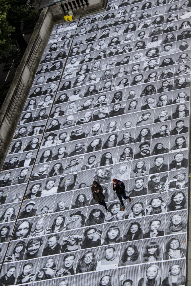 Numerous large black and white portrait photos pasted on the ground with two people walking over them.