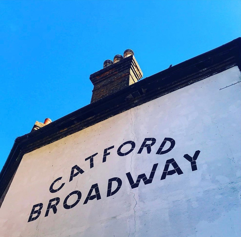 An image of a house painted white with the words 'CATFORD BROADWAY' in black and blue sky above