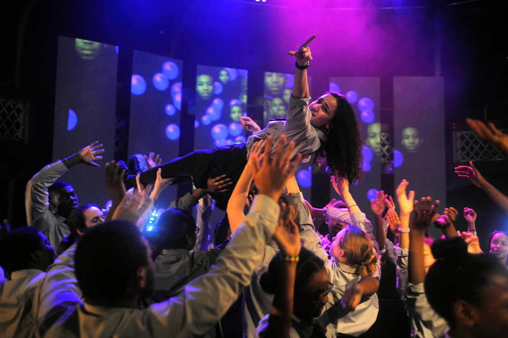 Group of children on stage holding a girl aloft with purple and blue lighting