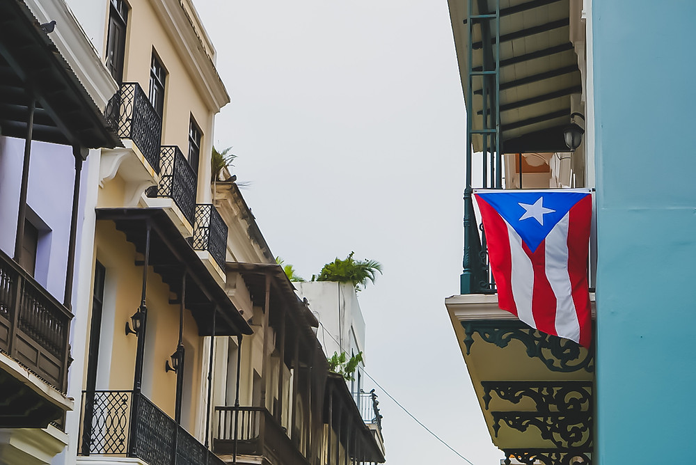 Photo of Puerto Rican flag on blue building, near beige building, under white sky.