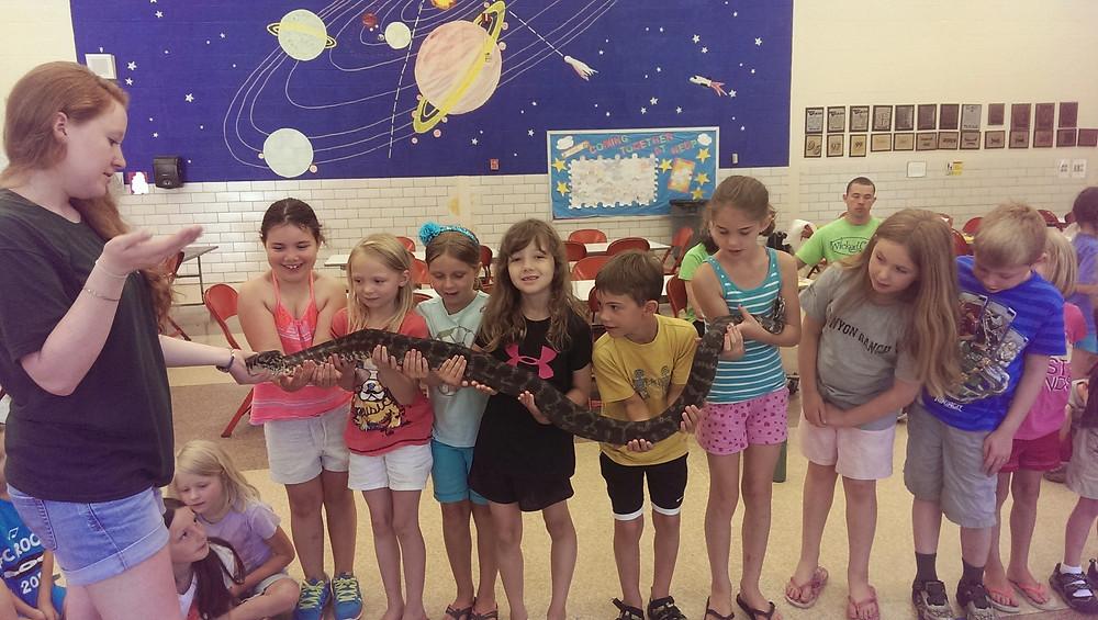 Vet School students holding a large snake