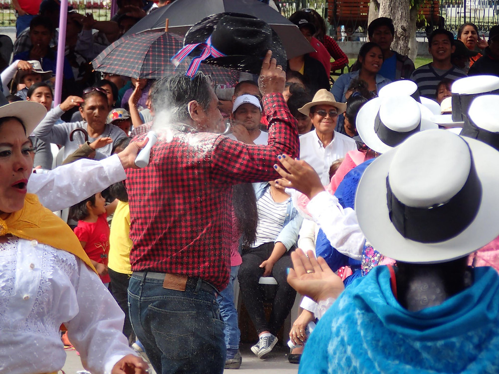 Man getting covered in talc in the Ayacucho festival.
