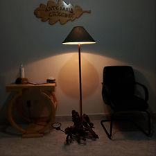 Lámpara de pie hecha con madera rescatada del río junto una mesa y una silla