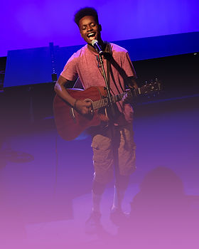 A young boy sings at a microphone with a guitar.