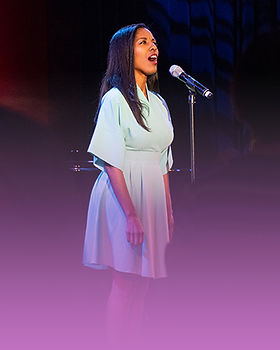 A woman sings at a microphone.