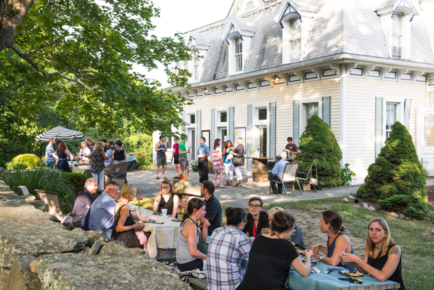 A private party outside the White House, where guests relax among the New England foliage.