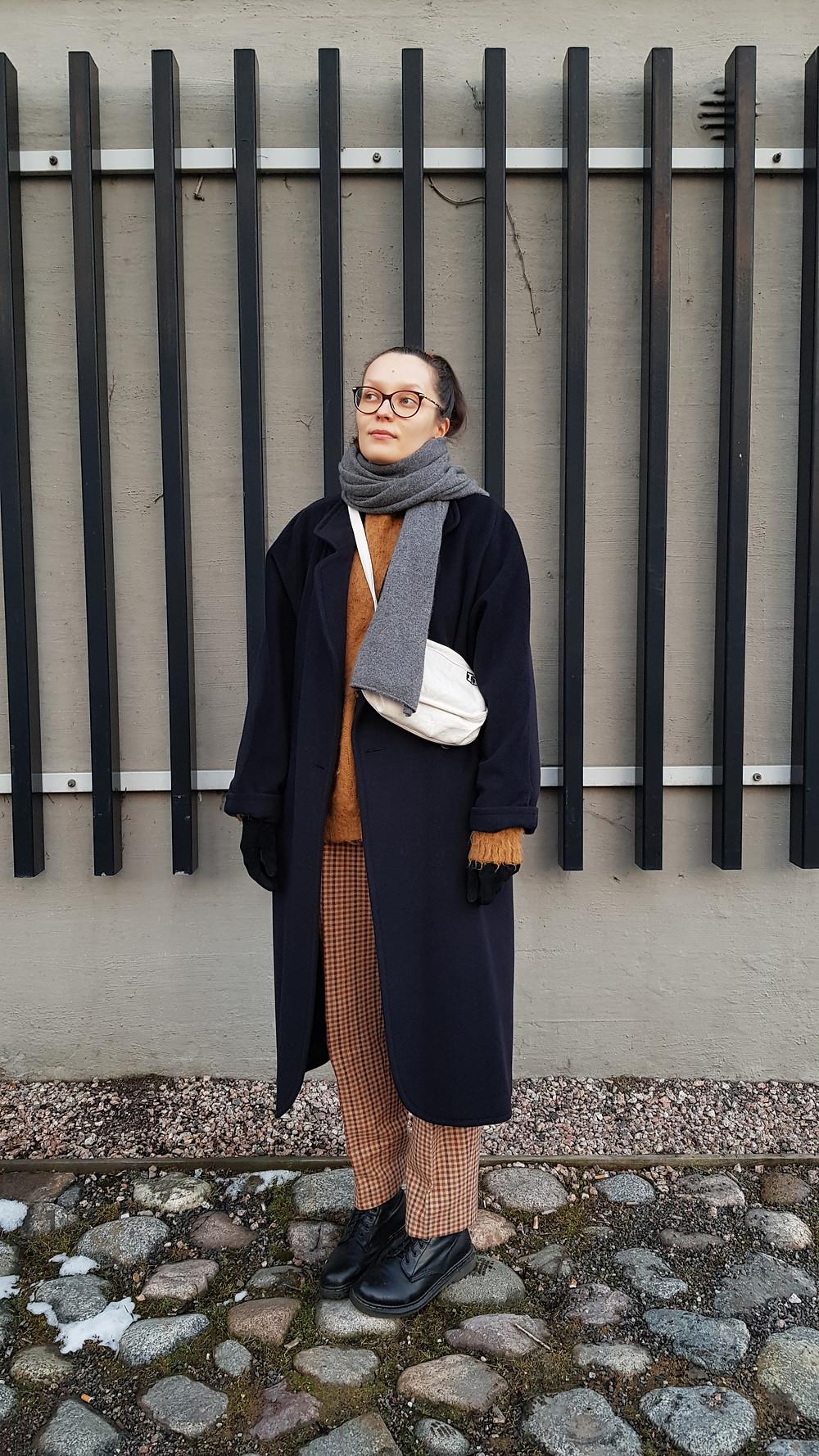 Kuvassa seison mukulakivetyksellä ja taustallani on mustista laudoista tehty paneeli. Katson yläviistoon ja päälläni on tummansininen takki, ruutuhousut ja maiharit.