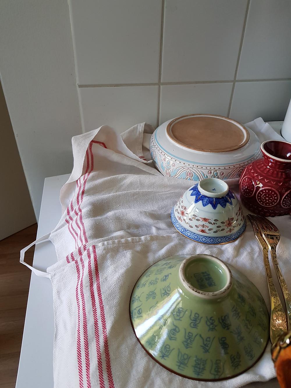 Kuvassa on erivärisiä etnisen tyylisiä astioita kuivumassa tiskipöydällä valkoisen liinan päällä.