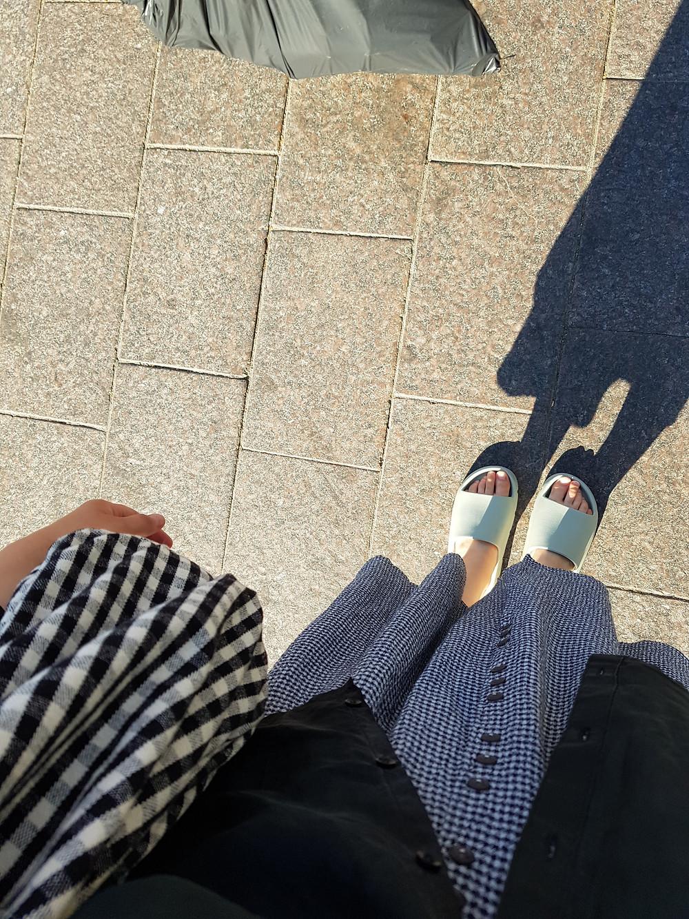 Kuva on jaloistani. Päälläni on mintunvihreät muoviset sandaalit, sinivalkoruudullinen hame, mustavalkoruudullinen laukku ja musta silkkipaita. Kuvan ylälaidassa on harmaa muovinen kauppakassi.