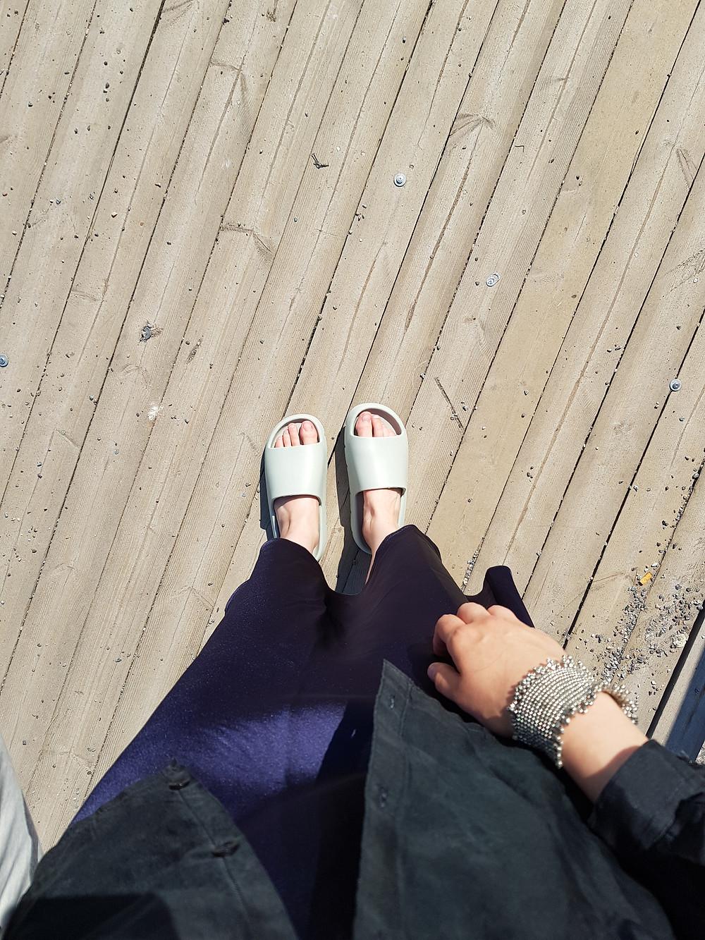 Kuva on otettu jaloistani. Päälläni on mintunvihreät muoviset sandaalit, tummansininen satiinihame, musta silkkikauluspaita ja kädessä hopeisista helmistä tehty leveä käsikoru.