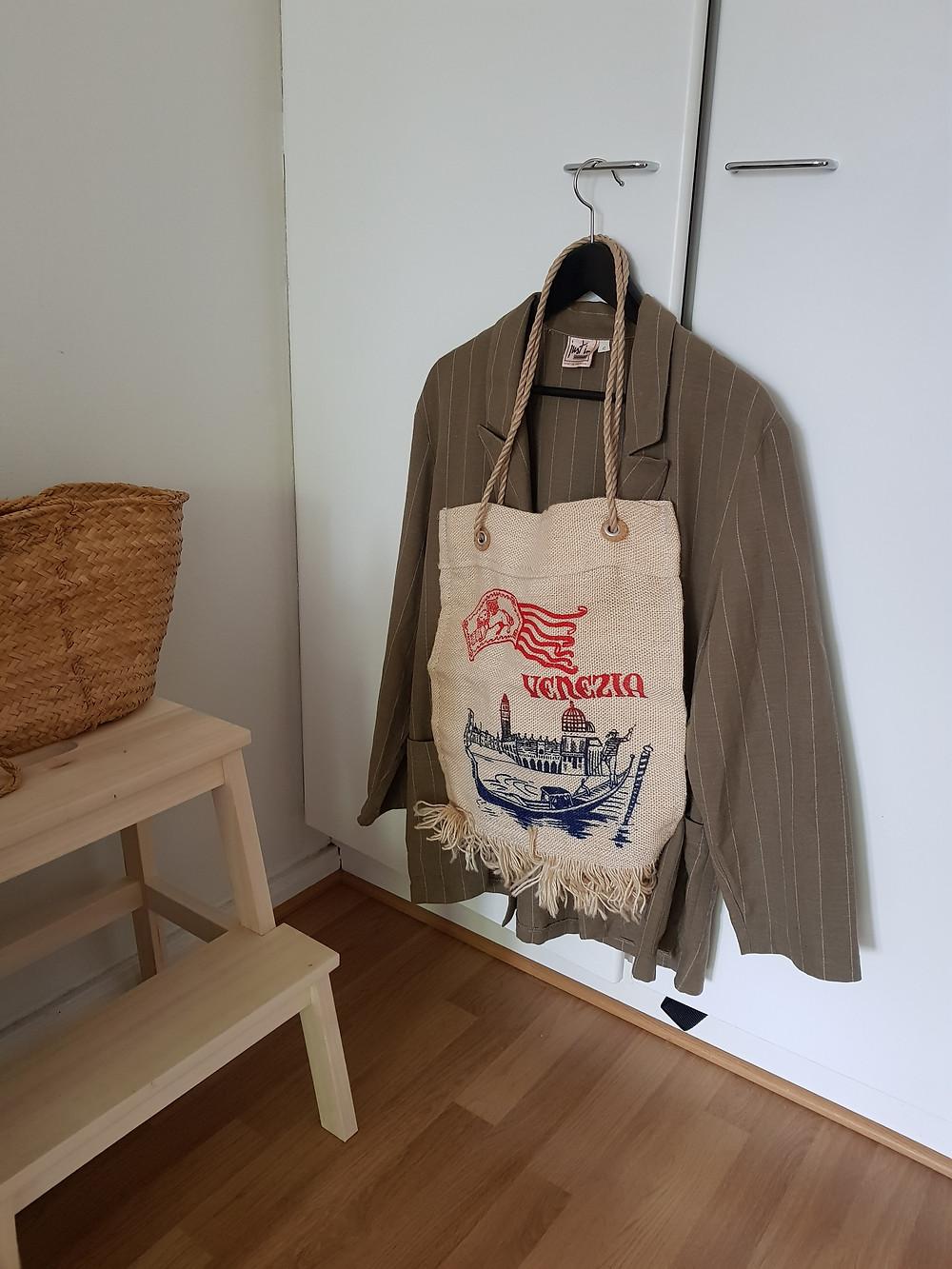 Kuva on otettu asuntoni nurkasta, jossa on puinen jakkara ja sen päällä korilaukku sekä vaatekaapin kahvasta roikkuva vihreä pellavableiseri ja Venetsia-teemainen laukku.