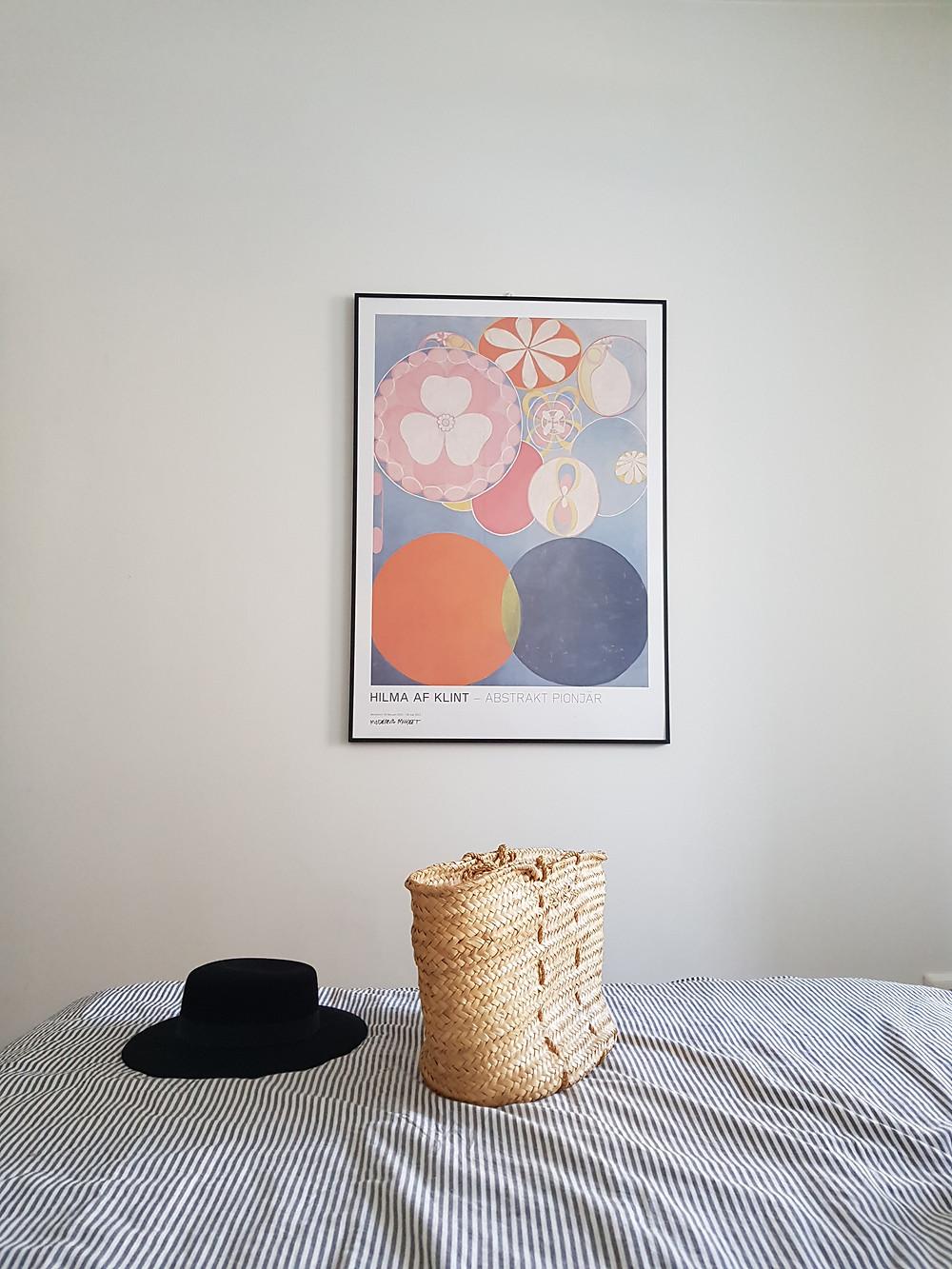 Kuva on otettu sängynpäädystä, sängyllä on valko harmaa raidalliset lakanat, sen päällä beige korilaukku ja musta lierihattu. Seinällä on julistetaulu Hilma f Klintin maalauksesta.