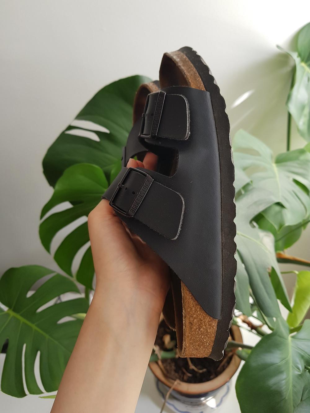 Pitelen käsissäni sandaaleita, jotka näkyvät sivusta päin. Taustalla vihreä peikonlehti.