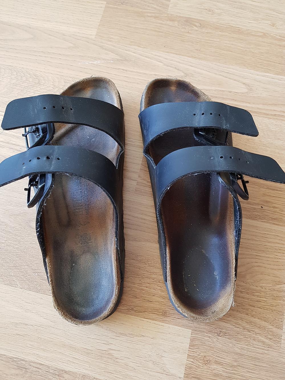 Välivaihekuva kahdesta sandaalista, joista vasemmalla puolella olevalla on vaaleampi, puhtaampi pohja mokkakivellä kumituksen jälkeen.