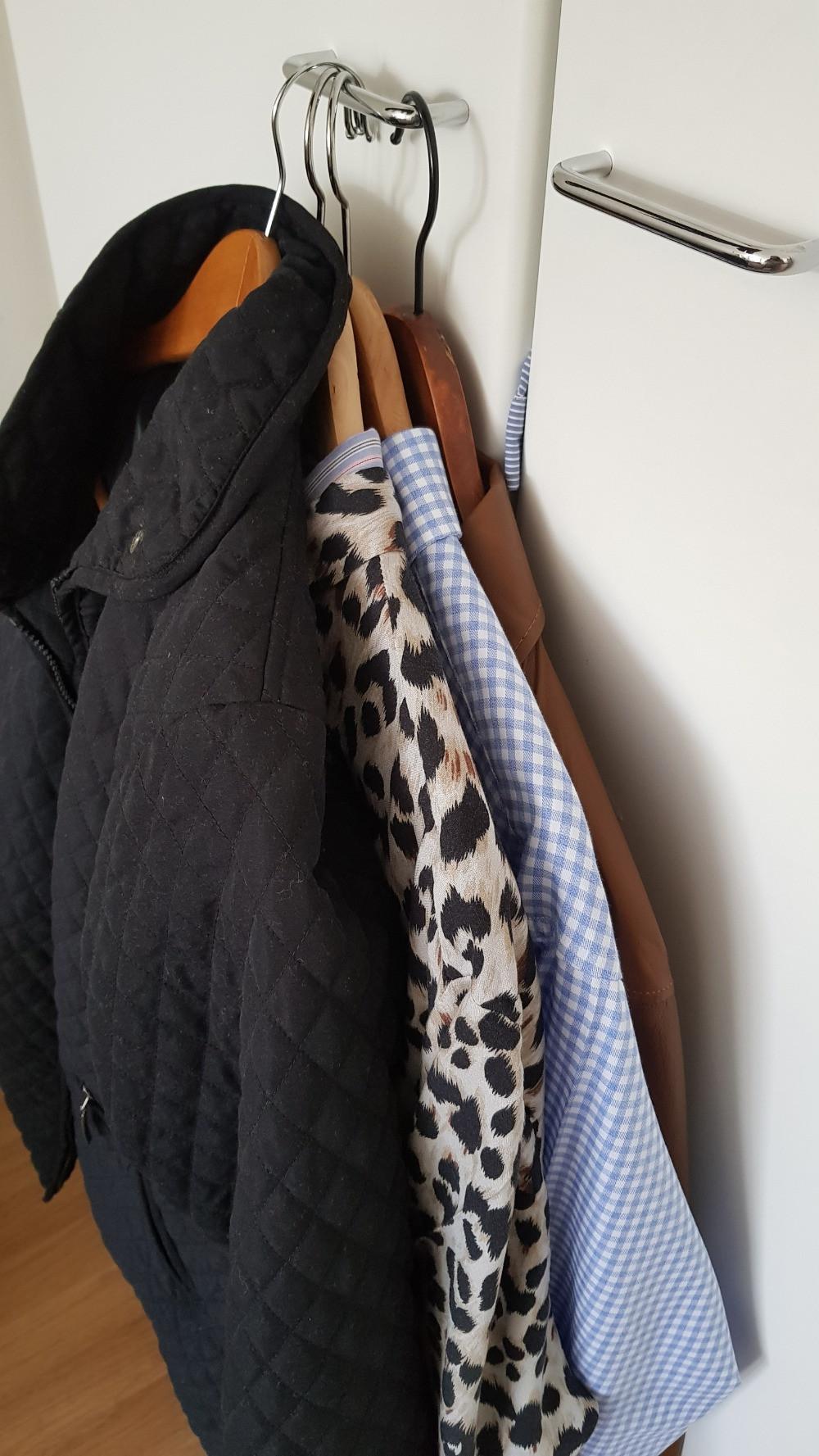 Kuvassa vaatekaapin ovenkahvassa roikkuu henkareissa musta tikkitakki, leopardikuosinen kauluspaita, sinivalkoruudullinen kauluspaita ja vaaleanruskea nahkakauluspaita.